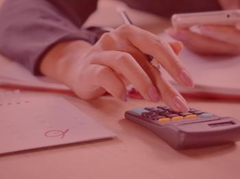 notícia: Empresa consegue retirar nome de cadastro de proteção ao crédito devido à pandemia. #pratodosverem: na foto, uma mulher com um celular e uma calculadora realizando contas. Em cima da mesa um calendário também. Cores na foto: branco, preto, verde, amarelo, rosa, azul e cinza.