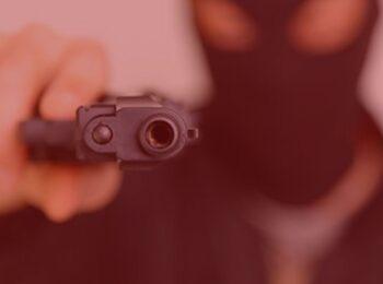 artigo: Responsabilidade do empregador por bens pessoais dos empregados. #pratodosverem: na foto, um homem com capuz está apontando uma arma. Cores na foto: preto, vermelho e marrom.