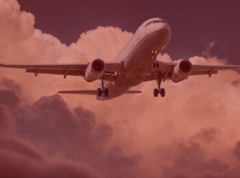 notícia: Decolar.com e cia aérea devem restituir pacote de viagem cancelado por coronavírus. #pratodosverem: na foto, um avião voando. Cores na foto: branco, cinza, vermelho, preto e azul.