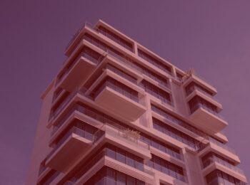 artigo: A ilegalidade de cobrança de taxa condominial antes da entrega das chaves do imóvel ao promissário comprador. #pratodosverem: na foto, um prédio. Cores na imagem: azul, vermelho, branco e preto.