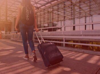 notícia: Companhia aérea indenizará passageira por atraso de 48 horas em voo. #pratodosverem: Na foto, uma mulher no aeroporto. Cores na foto: amarelo, preto, azul, prata, cinza e laranja.