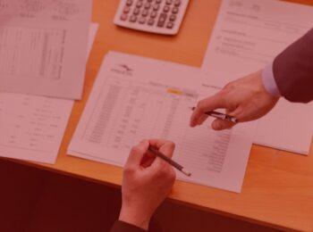 #pratodosverem: notícia: Banco indenizará por restrição de crédito indevida. Na foto, duas pessoas conversam sobre alguns papéis que estão sob a mesa. Cores na imagem: branco, prata, vermelho, marrom e amarelo.