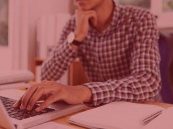 #pratodosverem: Banco indenizará cliente que pagou boleto fraudado. na foto um homem com a cabeça apoiada em seu braço olhando para o computador. cores na foto: marrom, branco, preto e prata.