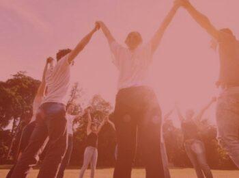 #paratodosverem: artigo: A necessidade da ressocialização do adolescente infrator. Na foto, jovens de mãos dadas e com os braços erguidos para o céu. Cores na foto: vermelho, branco, azul, preto e verde.