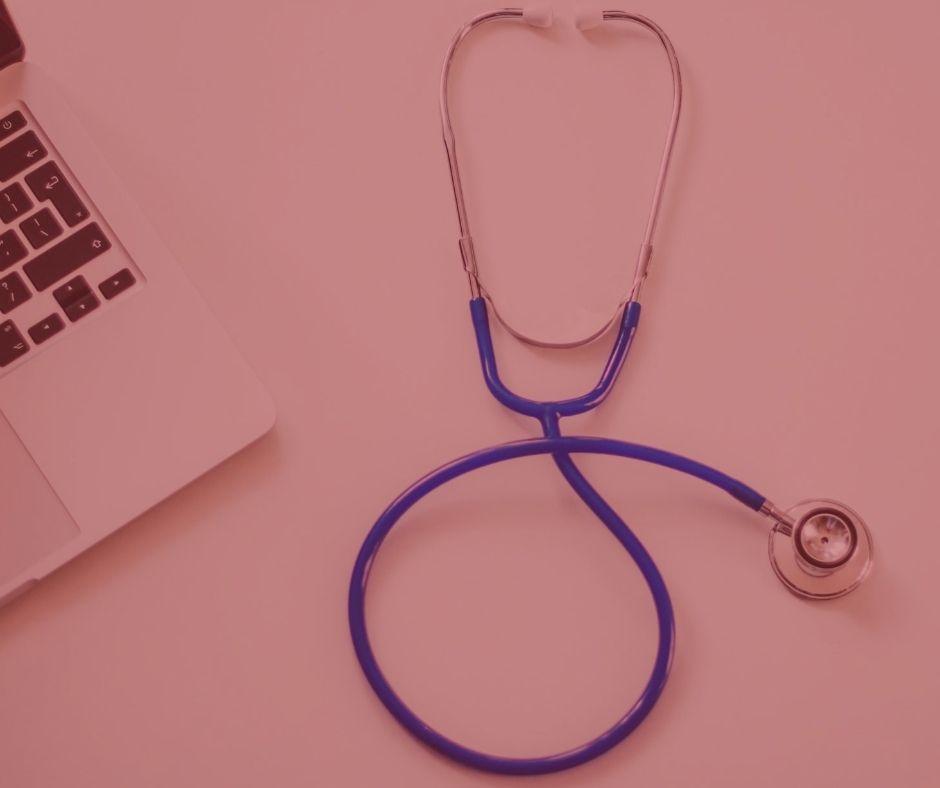 #pratodosverem: notícia: Plano de saúde deve fornecer medicamento para tratamento de asma. Na foto, um estetoscópio na cor azul com prata. Na mesa também encontramos um notebook prata com o teclado preto.