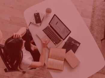 #pratodosverem: Home Office: quem trabalha nessa modalidade possui direito a horas extras? na foto, uma mulher trabalhando em casa. Cores na foto: preto, branco, cinza e marrom.