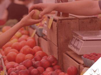 #pratodosverem: post: O vale-alimentação pode ser descontado do trabalhador ? - Na foto, uma pessoa realizando uma compra de frutas no mercado. Cores na imagem: vermelho, laranja, marrom, branco, preto e verde.