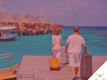 post: Quando um trabalhador tem direito a férias ? Na imagem um casal chegando para suas férias. Cores na foto: azul, amarelo, branco, cinza, laranja e marrom.