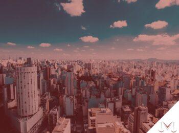 #pratodosverem: artigo: A intervenção pública e a contribuição de melhoria. Na foto, uma cidade com vários prédios. Cores na imagem: azul, branco, amarelo, cinza, bege.