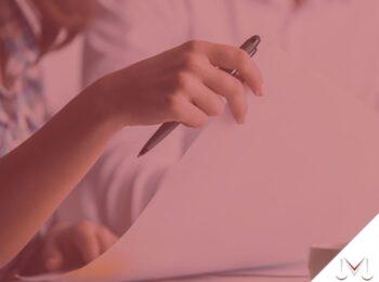 #pratodosverem: Meu empregado faleceu, quais os direitos trabalhistas que terei que pagar? Na foto uma mulher esta conversando e segurando alguns papeis para assinar. Cores na imagem: vermelho, branco, preto, cinza e azul.