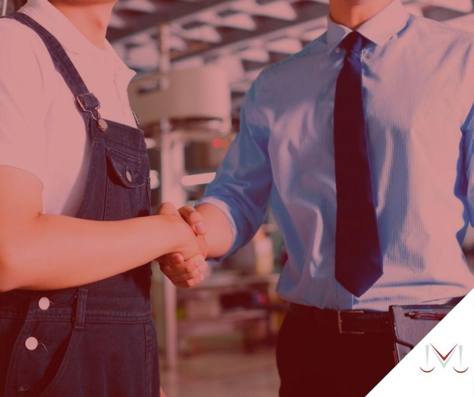 #pratodosverem: artigo: Responsabilidade do empregado. Na foto um gerente conversando com um outro funcionário da empresa, os dois estão se cumprimentando. Cores na imagem: branco, azul, preto e vermelho.