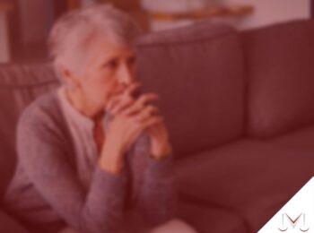 #pratodosverem: post: Pensão por morte é direito de quem da família? Na foto uma idosa sentada no sofá com as mãos na cabeça. Cores na imagem: vermelho, cinza, marrom e branco.