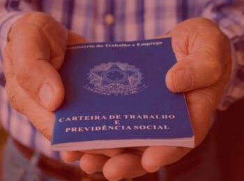 #pratodosverem: artigo: seguro-desemprego. Na foto uma pessoa segurando a carteira de trabalho. Cores na imagem: azul, branco, marrom, dourado.