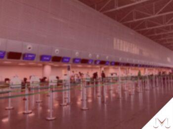 #pratodosverem: post: Se o seu voo está atrasado, você tem direito a indenização? Na foto a área de check-in de um aeroporto. Cores na imagem: vermelho, azul, verde, cinza e azul.