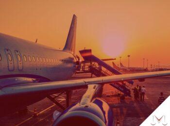#pratodosverem: na foto um avião parado no aeroporto enquanto as pessoas estão embarcando. Cores na imagem: branco, azul, amarelo. laranja e branco.