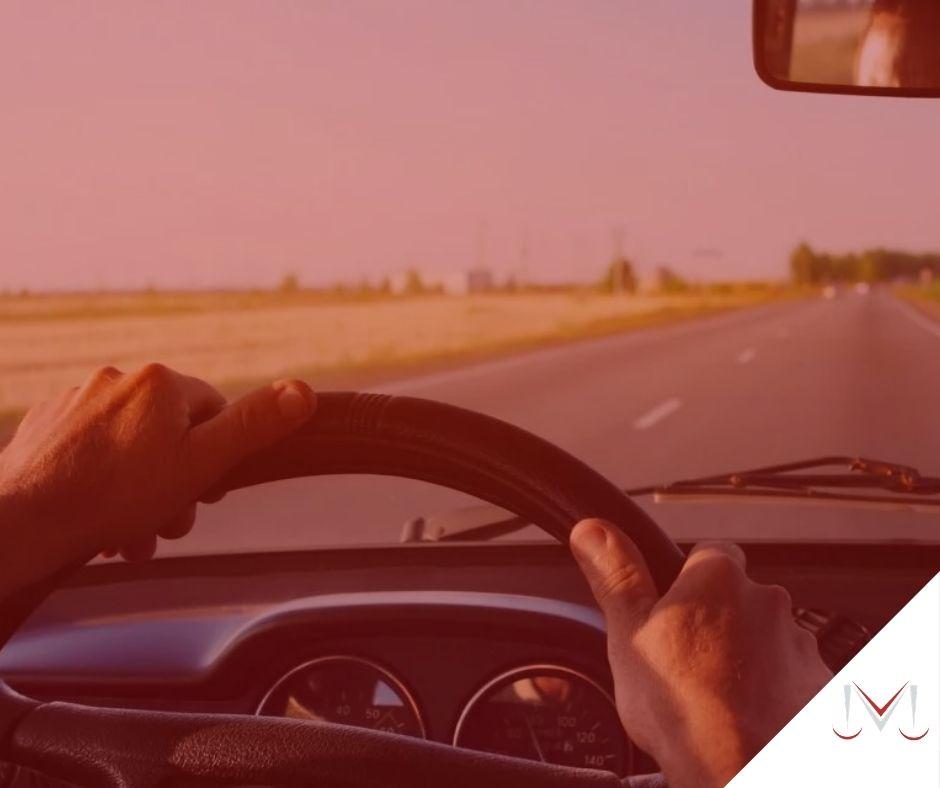 #pratodosverem: post: Eu devo ganhar horas extras por deslocamento de cidade? Na foto, uma pessoa dirigindo um veículo na estrada. Cores na imagem: verde, preto, branco e cinza.