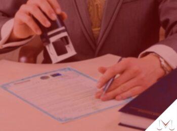 retomada da utilização do nome de solteiro sem realizar divórcio e/ou dissolução de união estável. Na foto uma pessoa carimbando um registro. Cores na imagem: azul, dourado, preto, branco.