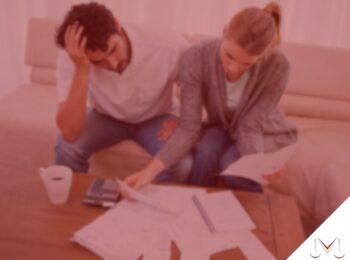 #pratodosverem: post: Posso ser cobrado por dívida realizada por meu cônjuge? Na foto, um casal olhando as contas do mês. Cores na imagem: vermelho, branco, marrom, prata e cinza.
