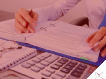 #pratodosverem: artigo: Revisão de benefícios e operação pente-fino. Na foto, uma pessoa analisando documentos que estão em cima da mesa. Cores na imagem: azul, branco, preto, prata, vermelho e dourado.