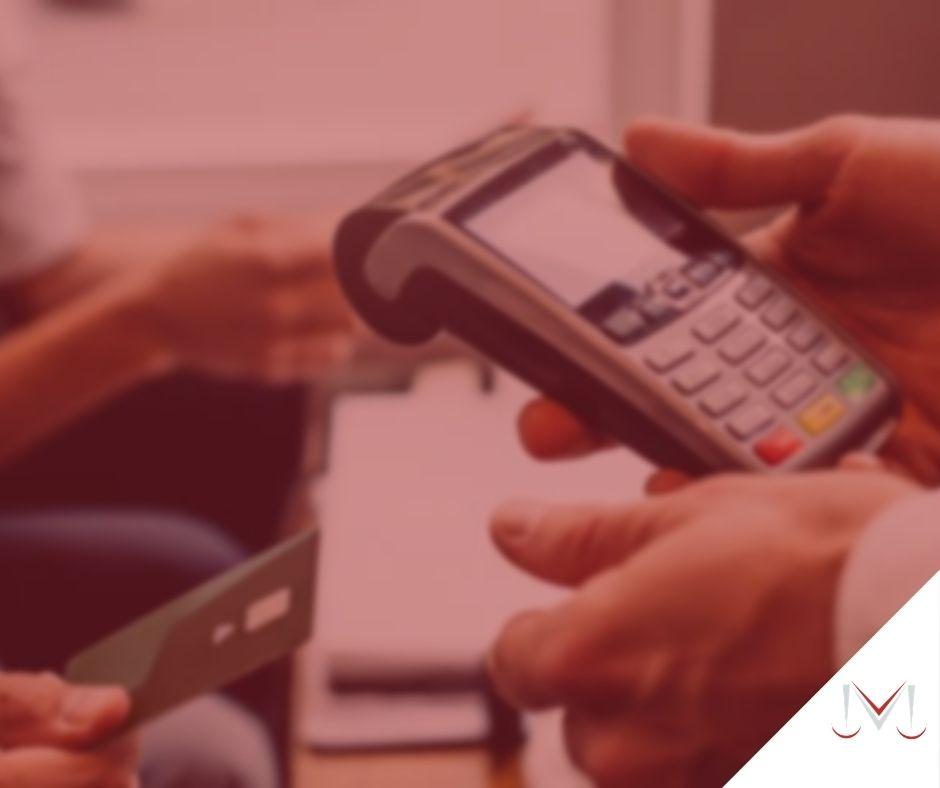"""#pratodosverem: artigo: Repassar a taxa da """"maquininha"""" ao cliente. Na foto uma pessoa pagando uma compra com cartão e a outra segurando uma maquininha de cartão. Cores na imagem: preto, amarelo, vermelho, verde e azul."""