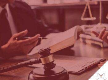 #pratodosverem: artigo: Atrasar pagamento de rescisão quando empregado morre gera multa? - na foto uma pessoa esta conversando com a outra e lendo um livro. Cores na imagem: branco, preto, marrom, dourado e azul.