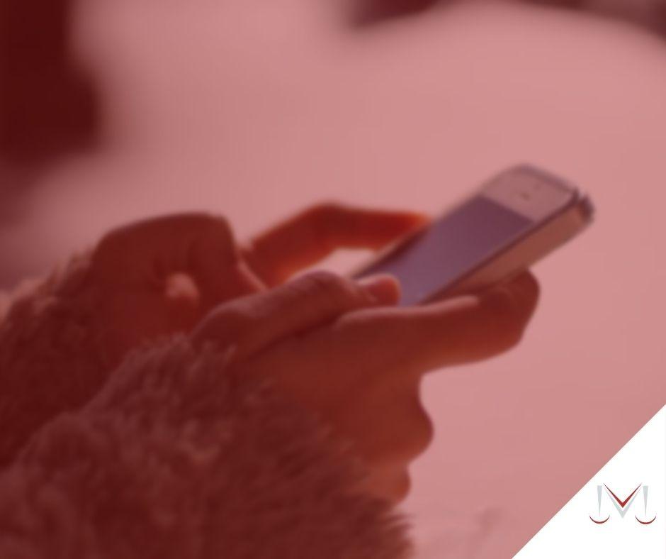 #pratodosverem: artigo: Posso requerer indenização por demissão pelo Whatsapp? - Na foto uma pessoa está mexendo no telefone celular. Cores na imagem: vermelho, branco e azul.