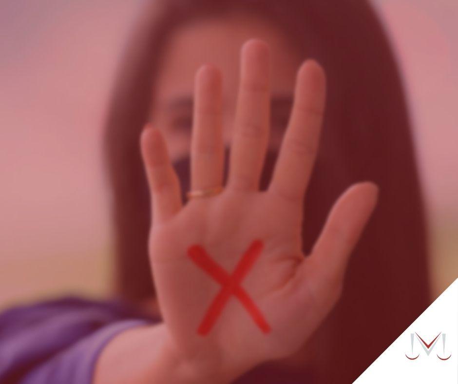 """#pratodosverem: artigo: Sinal vermelho contra a violência doméstica. Descrição da imagem: uma mulher com a letra """"X"""" desenha na mão. Cores na imagem: roxo, vermelho, dourado e branco."""