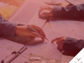 #pratodosverem: artigo: A solidariedade do casal no pagamento de dívidas. Na foto um casal está conversando sobre algumas contas que estão em cima da mesa. Cores na imagem: azul, amarelo, branco, laranja, vermelho e preto.