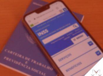 #pratodosverem: artigo: Prova de vida e os meios de facilitação. Na foto um celular e uma carteira de trabalho estão em cima de uma mesa. Cores na imagem: azul, branco, marrom e verde.