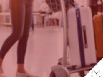#pratodosverem: artigo: O que fazer quando sua bagagem for extraviada? Na foto uma mulher esta no aeroporto carregando suas bagagens. Cores na imagem: vermelho, branco, laranja, azul, preto e branco.