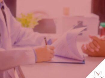 #pratodosverem: artigo: Alta do INSS, mas a empresa não me considera apto para o retorno. O que fazer? Descrição da imagem: um médico assinando documentos para um paciente. Cores na imagem: verde, branco, azul, preto e rosa.