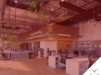 #pratodosverem: artigo: O que é o marco legal das Startups? Descrição da imagem: um coworking onde as pessoas trabalham. Cores na imagem: cinza, preto, marrom, amarelo, verde, azul e laranja.