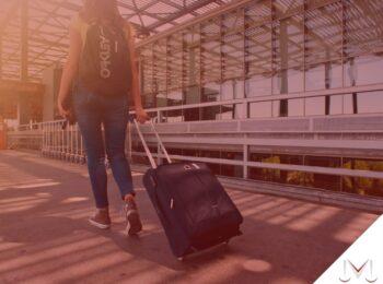 #pratodosverem: artigo: O empregado pode perder ou ter reduzida as férias? Descrição da imagem: uma mulher esta com suas malas de viagem andando pelo aeroporto. Cores na foto: preto, marrom, preto ,azul, branco e verde.