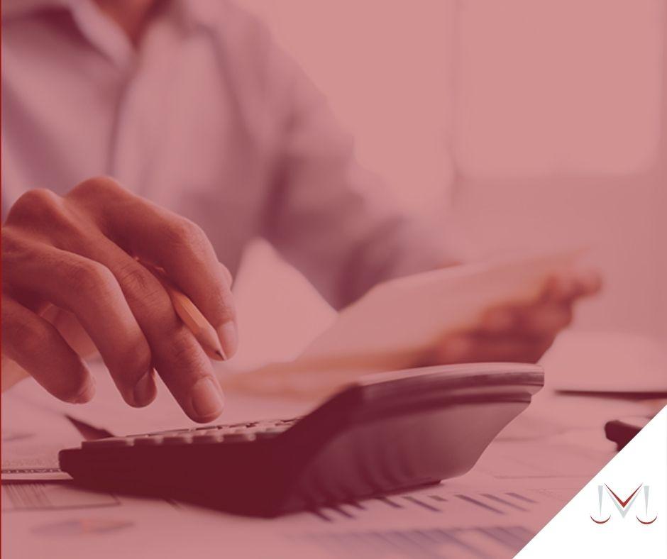 #pratodosverem: artigo:O que mudou com a lei do superendividamento? Descrição da imagem: um homem fazendo contas na calculadora. Cores na imagem: vermelho, branco, azul e preto.