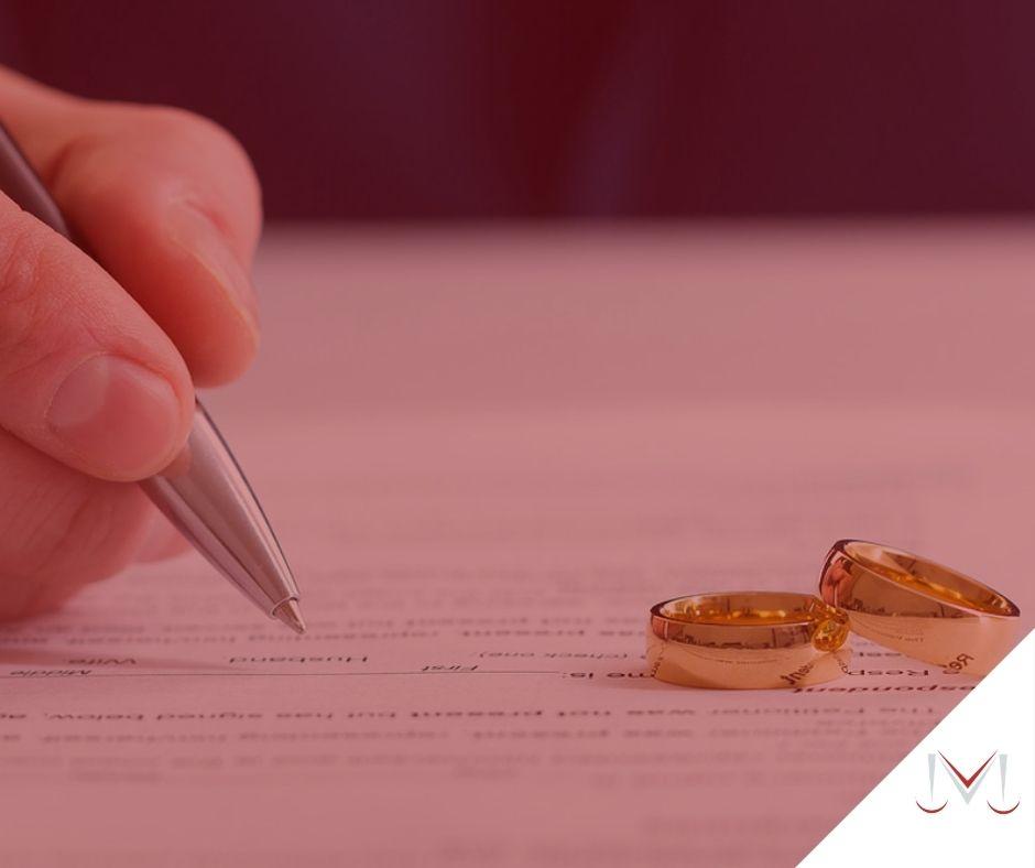 #pratodosverem: artigo: Divórcio post mortem. Descrição da imagem: uma pessoa assinando o divórcio com suas alianças em cima da mesa. Cores na imagem: branco, vermelho, cinza, prata, dourado e preto.