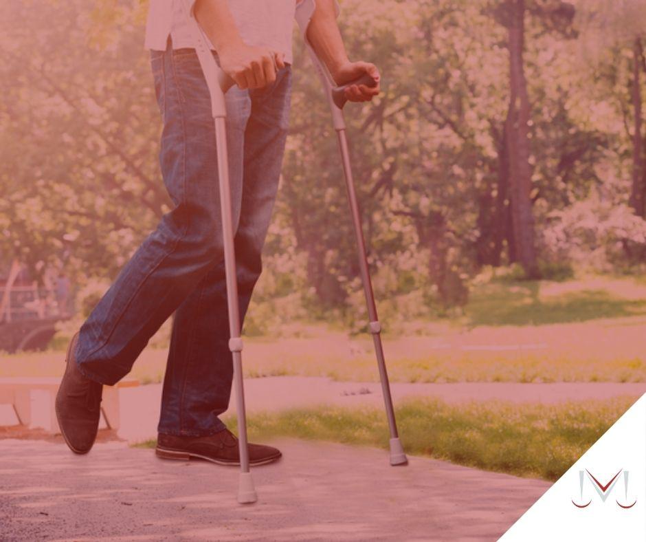 #pratodosverem: artigo: A aposentadoria por incapacidade e o adicional de 25%. Descrição da imagem: uma pessoa utilizando muletas está em um parque. Cores na foto: vermelho, cinza, azul, branco e prata.