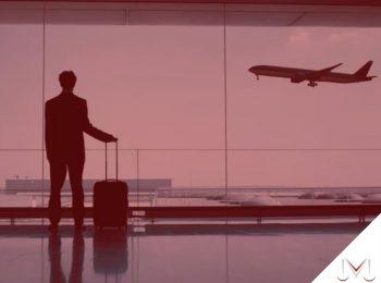 #pratodosverem: artigo: Férias concedidas fora do prazo. Descrição da imagem: um homem está no aeroporto com sua bagagem na mão. Cores na foto: vermelho, cinza, preto e azul.