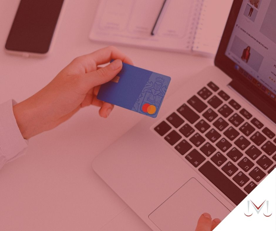 #pratodosverem: artigo: O simples envio de cartão de crédito não solicitado pelo cliente não gera dano moral. Descrição da imagem: uma pessoa segurando um cartão na mão e digitando no computador. Cores na foto: azul, preto, prata, cinza, branco e vermelho.